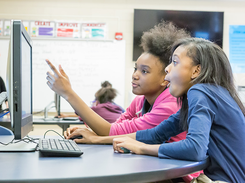 Girls in a classroom learning to code