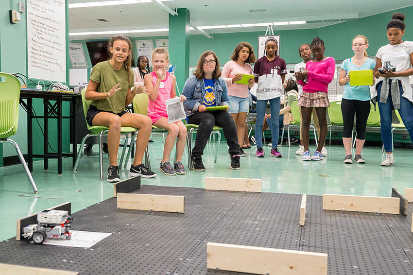 Girls program small battery-powered cars to travel through a maze using a tablet computer